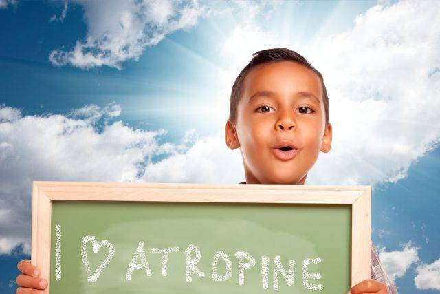 Child holding blackboard with I 'heart' atropine